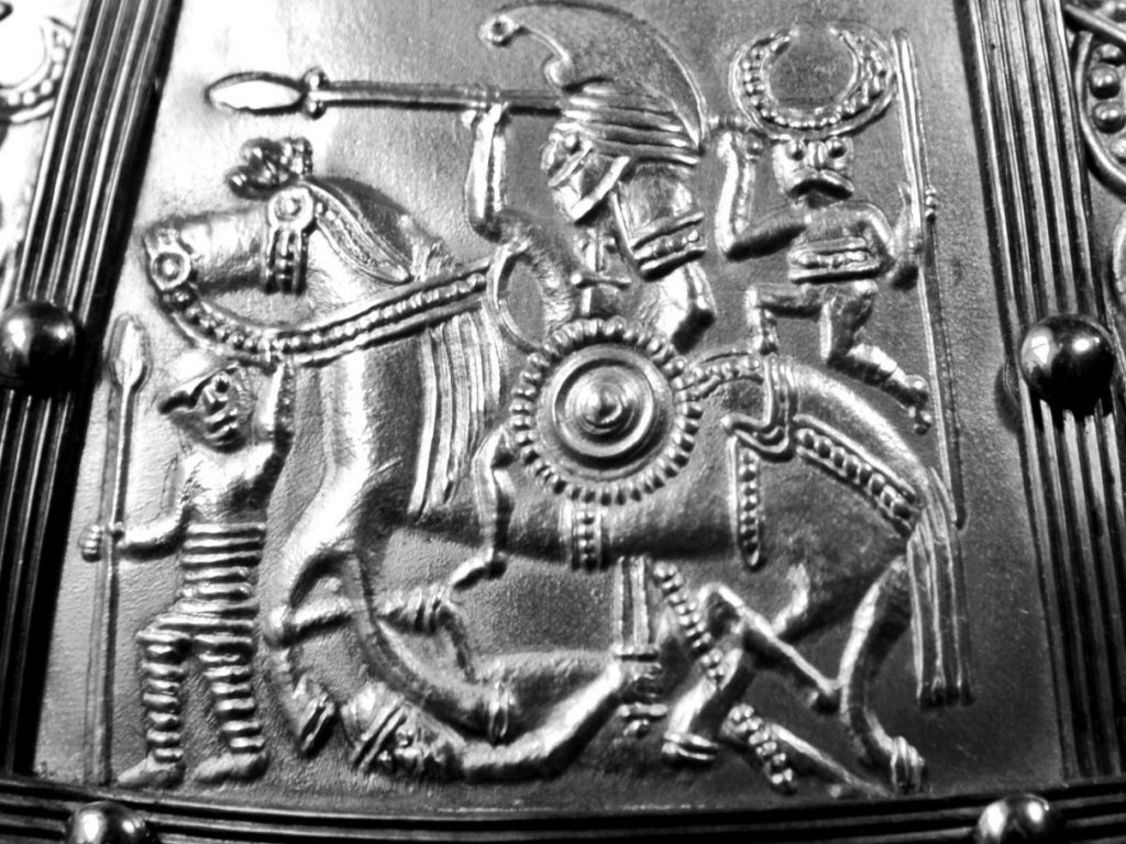 In battle, the Marlow warrior may have looked like this mounted sixth century war band leader (as portrayed on helmets found in England and southern Scandinavia). He is shown, armed with spear, sword and shield, trampling an enemy